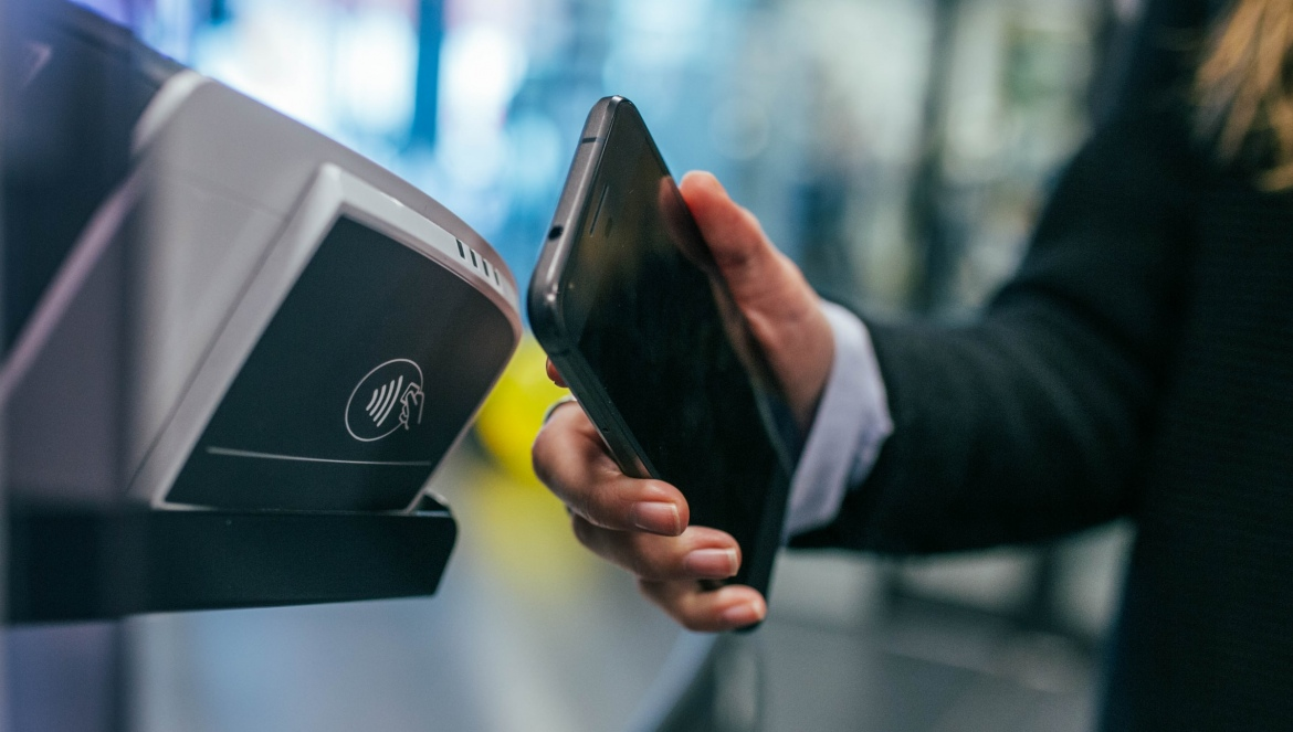 A woman holding her mobile phone points to a contactless payment terminal in Ghent, Belgium
