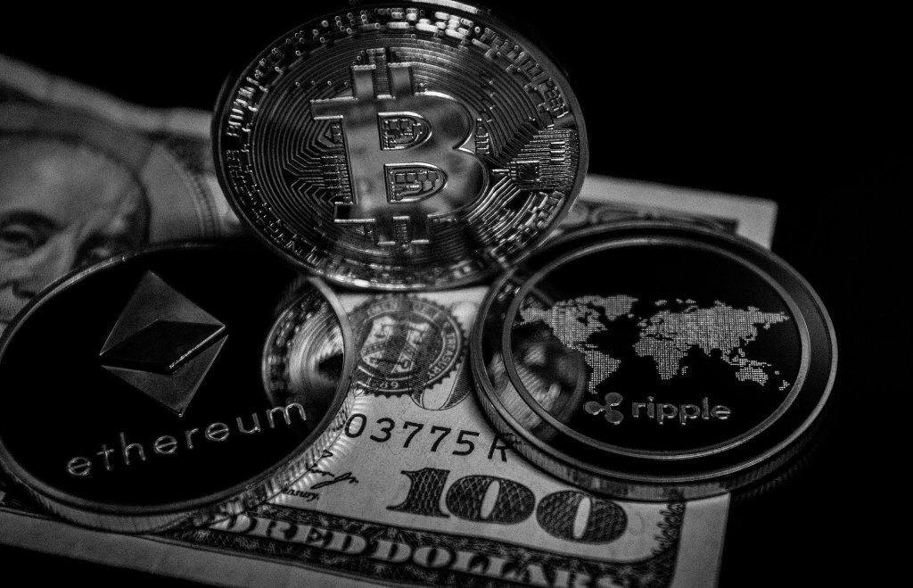 Cryptocurrency coins of different brands Bitcoin, Ethereum and Ripple are kept atop a 100 dollar US bill